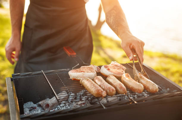 Crop man cooking meat in countryside stock photo