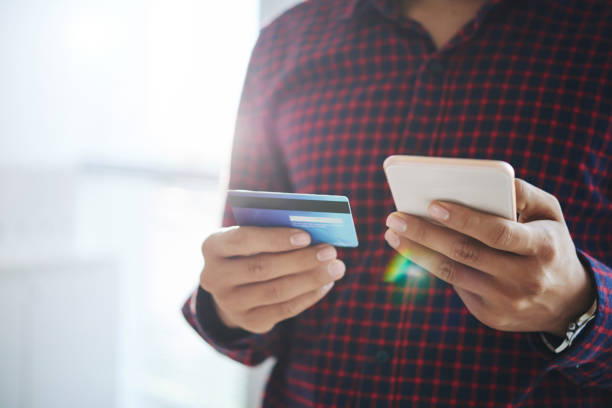 Crop man using smartphone with credit card Close-up shot of faceless man in shirt doing purchase online via smartphone with help of credit card convenience stock pictures, royalty-free photos & images