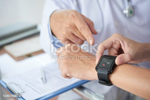Hands of anonymous patient using fitness tracker to show medical practitioner hear rate during checkup in doctor's office
