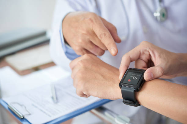 Crop patient showing heart rate to doctor Hands of anonymous patient using fitness tracker to show medical practitioner hear rate during checkup in doctor's office fitness tracker stock pictures, royalty-free photos & images