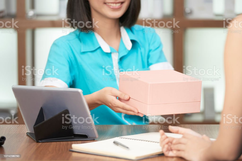 Crop shot of smiling spa salon receptionist giving beauty box to...