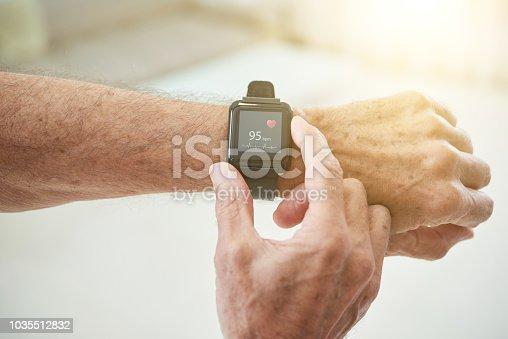 Crop shot of elderly man measuring pulse with modern smart watch in sunlight