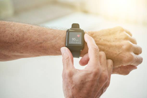 ernte senior woman messen puls mit smart-watch - pulsmessung stock-fotos und bilder
