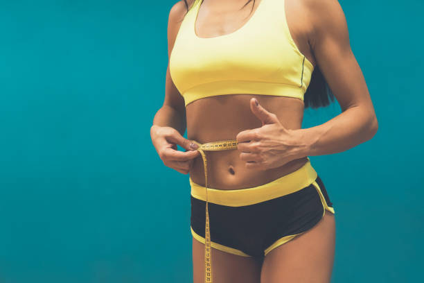 Crop shot of fitness woman in sport outfit measuring waistline with metric tape and showing thumb up. Good results of exercising in gym. Perfect shape of sportswoman. Achievments in body perfection. stock photo