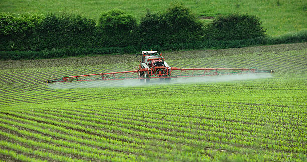 Crop spraying Tractor spraying newly sown crops herbicide stock pictures, royalty-free photos & images