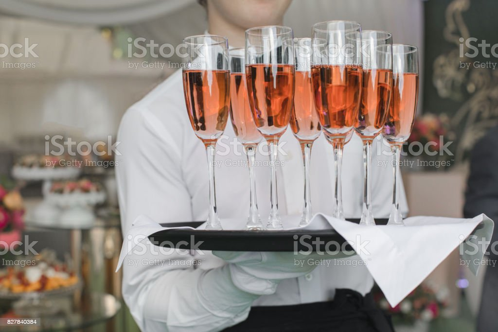 Crop waiter holding tray with glasses stock photo