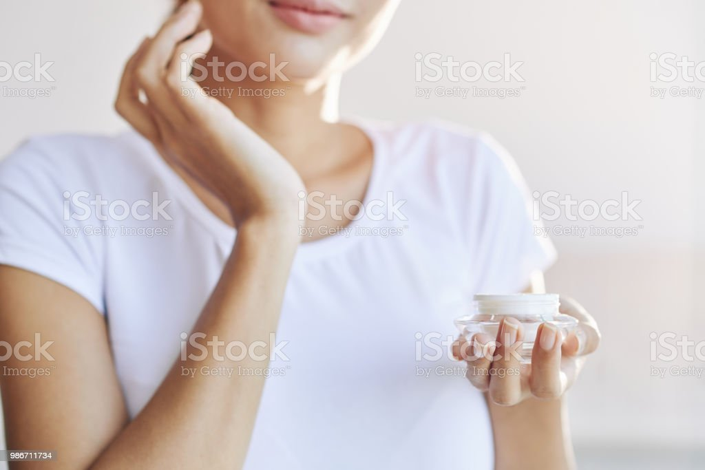 Crop woman applying?cream on face stock photo