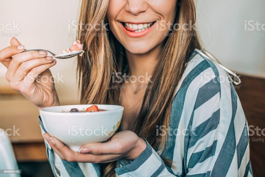 Crop woman close up eating oat and fruits bowl for breakfast stock photo