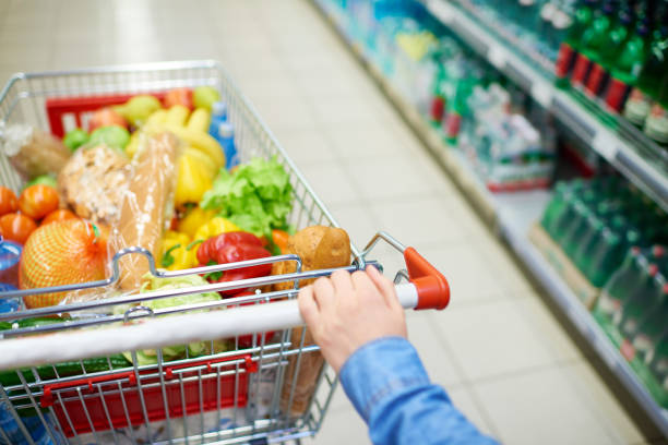 Crop woman pushing cart with products stock photo