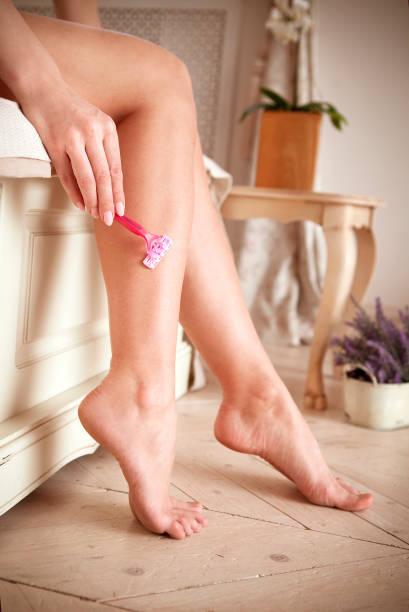 Recortar mujer afeitarse la pierna en casa - foto de stock