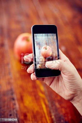 Crop woman using phone and picturing fresh ripe apple on rustic wooden surface