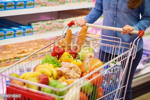 Faceless woman in denim shirt standing in supermarket with shopping cart full of healthy food