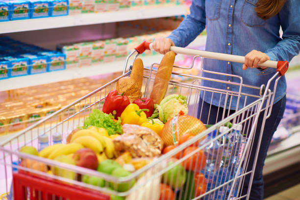 Crop woman with cart full of food Faceless woman in denim shirt standing in supermarket with shopping cart full of healthy food full stock pictures, royalty-free photos & images