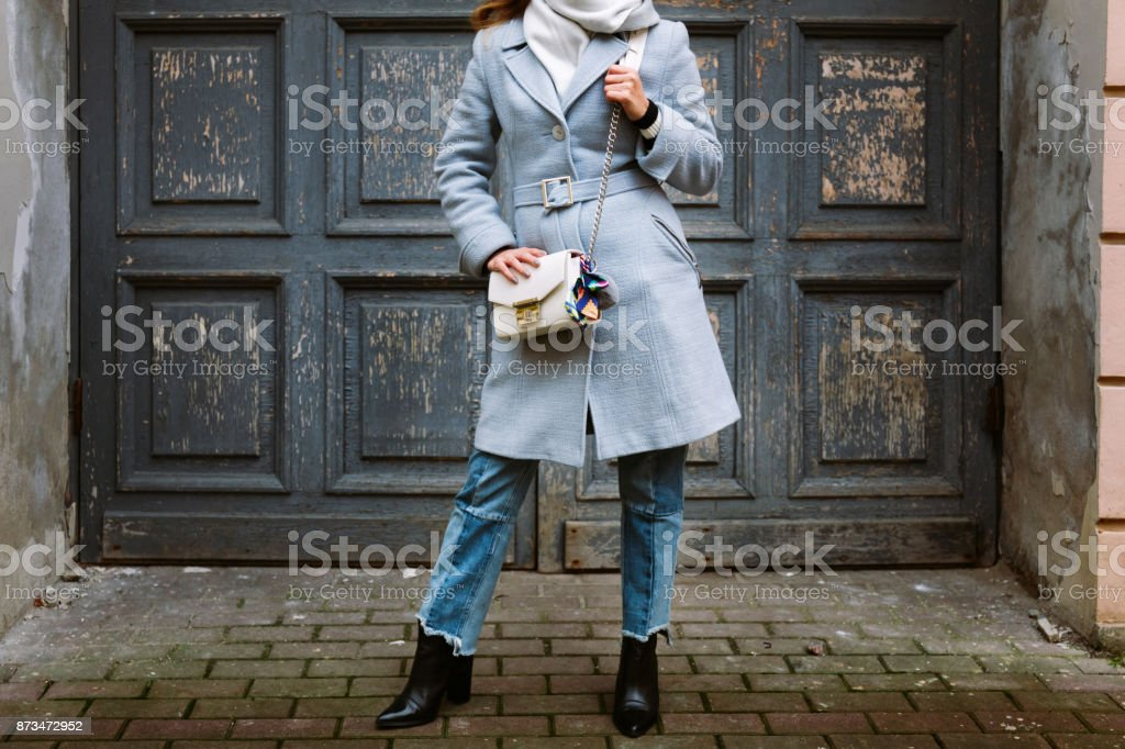 Croped picture at fashion handbag girl posing on street. Model looking aside. Lady wearing stylish autumn clothes. stock photo