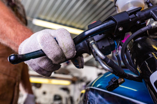 Croped view of man working in garage repairing motorcycle Croped view of man working in garage repairing motorcycle and customizing vehicle clutch stock pictures, royalty-free photos & images