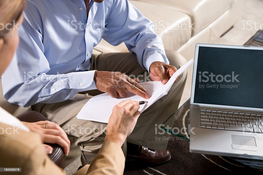 Cropped African American man and Caucasian woman pointing to doc stock photo
