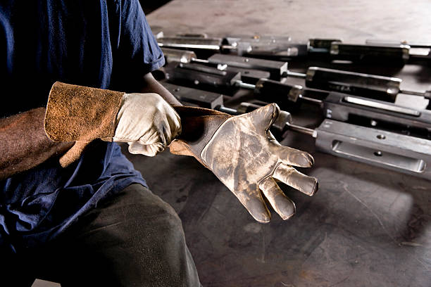 Cropped African American worker donning gloves stock photo