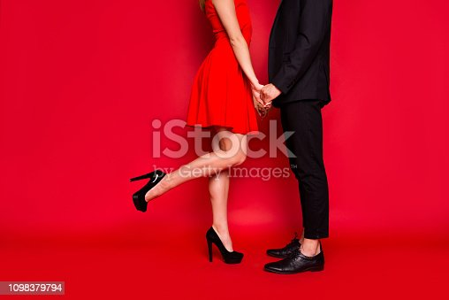 Cropped body legs of two nice elegant imposing trendy luxury stylish gorgeous people holding hands dancing entertainment isolated over bright vivid shine red background
