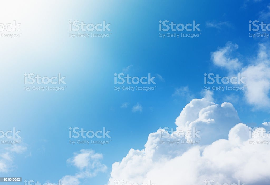 Cropped bright sun shining over floating cumulus clouds stock photo