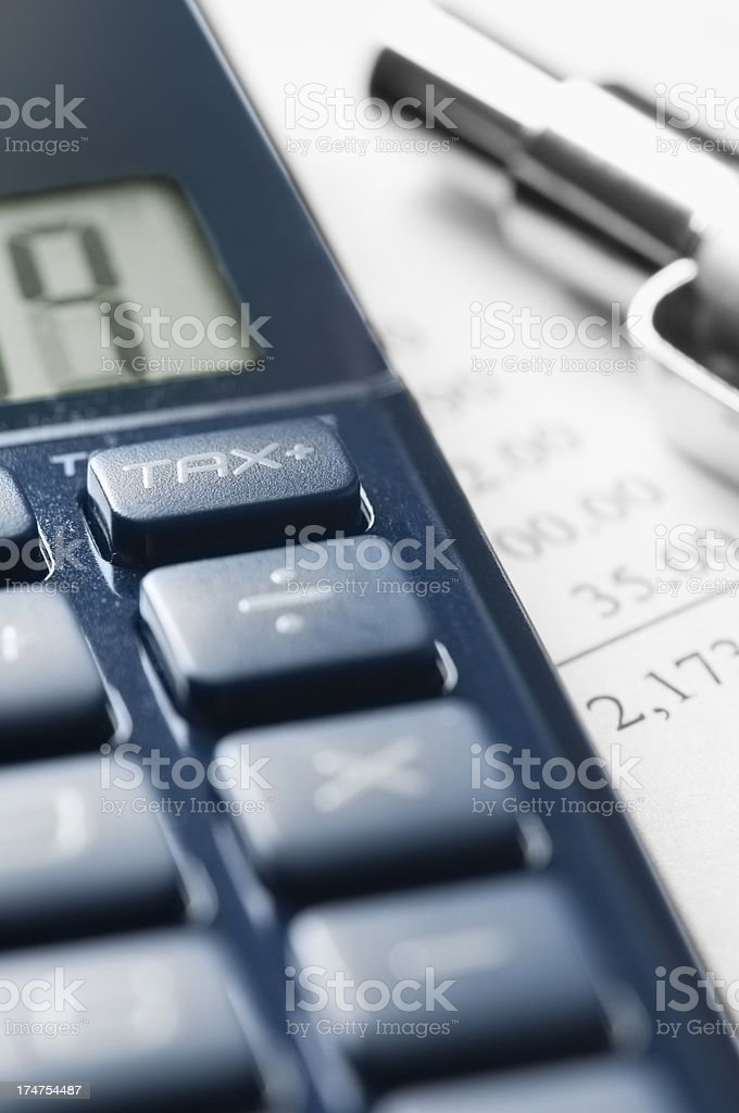 Cropped calculator with financial figures and pen royalty-free stock photo