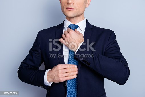 973213156 istock photo Cropped close up half face portrait of stunning, perfect man correcting tie, preparing for event, conferention, standing over gray background 932259882