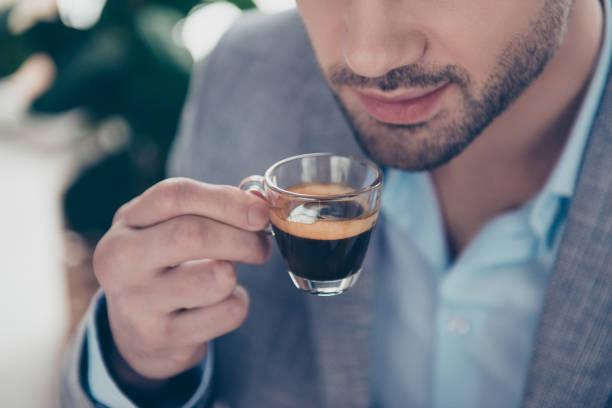 halbes gesicht porträt des stilvollen attraktiver mann mit kleinen glas espresso in der nähe von mund, jedes morgenritual am vor der arbeit arbeitsplatz hautnah abgeschnitten - espresso stock-fotos und bilder