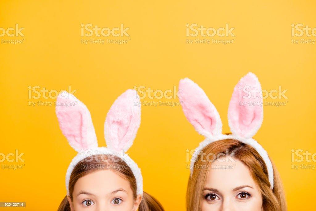 トリミング興奮して陽気な美しいママと小さな甘い遊び心のある面白い素敵な柔らかい娘バニーの耳が黄色の背景上に分離されて身に着けているハーフ顔の肖像画の写真をクローズ アップ ストックフォト
