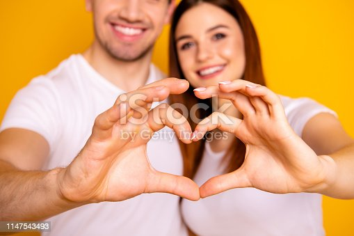 950598260 istock photo Cropped close up photo amazing beautiful she her he him his guy lady arms fingers make heart figure form romance mood hugging sincere wear casual white t-shirts outfit isolated yellow background 1147543493