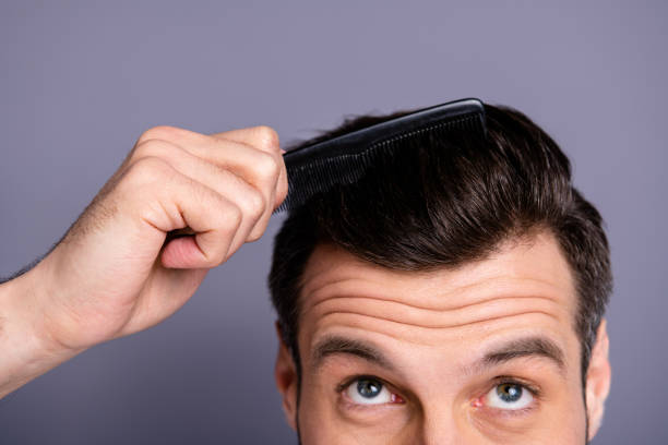 cropped close up photo amazing he him his macho hands arms plastic hair styling brush take care hairdo barber shop stylist visit look up process experiment wear white t-shirt isolated grey background - grosso imagens e fotografias de stock