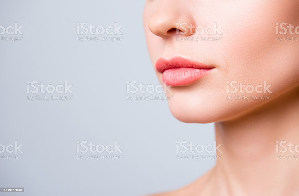 Cropped close up photo of beautiful woman's lips with shape correction, isolated on grey background, copyspace stock photo