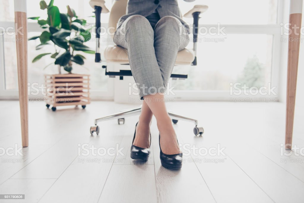 Cropped close up photo of healthy beautiful elegant woman's legs wearing high-heeled shiny black shoes, the woman is sitting in office at the table on modern luxurious armchair royalty-free stock photo