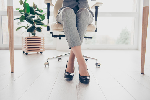 Cropped close up photo of healthy beautiful elegant woman's legs wearing high-heeled shiny black shoes, the woman is sitting in office at the table on modern luxurious armchair
