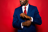 Cropped close up photo of sale manager entrepreneur chic employee employer occupation leadership gentleman groomed man correct cufflink fasten clasp on wrist isolated on red bright background