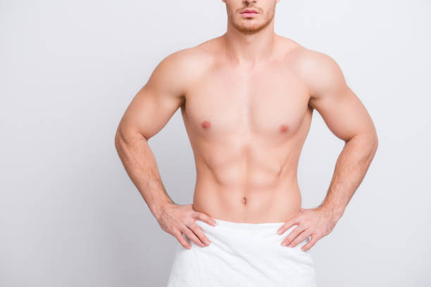 cropped close up photo of shirtless sexy tempting muscular attractive man's torso, man is keeping hands on hips isolated on gray background copy-spac - a petto nudo foto e immagini stock