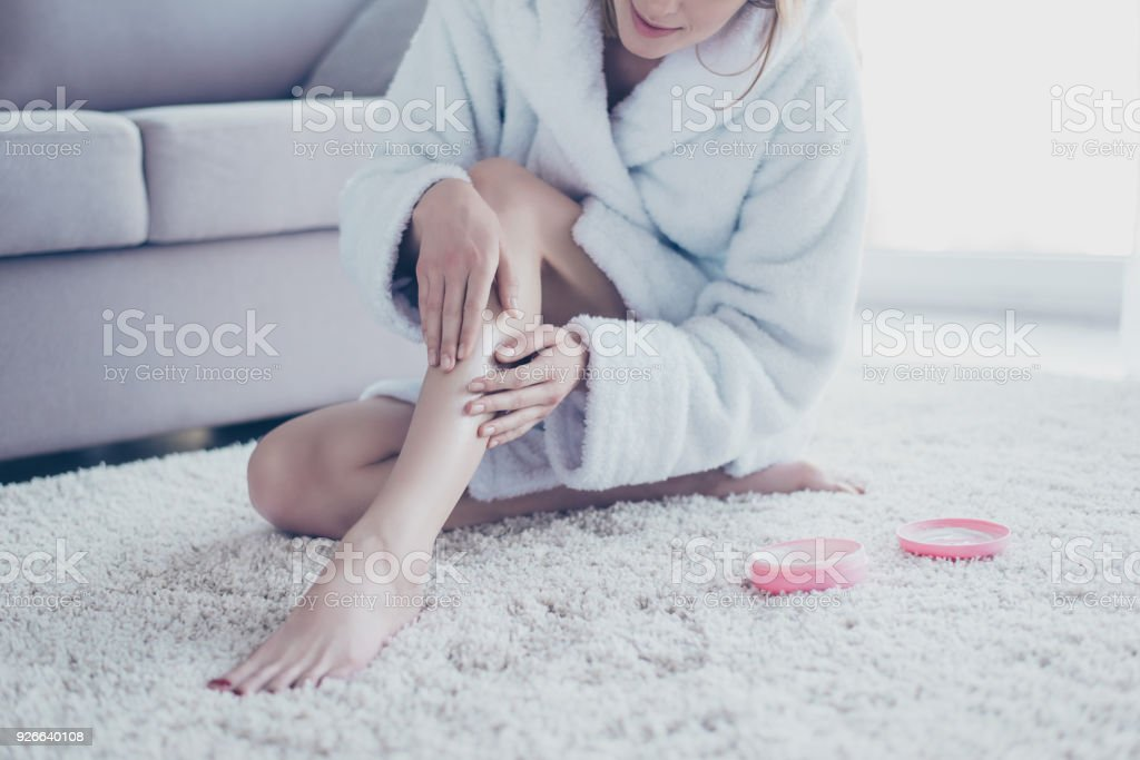 Cropped close up photo of woman wearing white bathrobe, she is sitting on the floor and applying moisturizing cream on her legs and nails after depilation and taking a shower stock photo