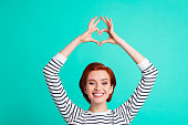 istock Cropped close up portrait of beautiful cute foxy ginger she her lady fingers hands up above head in figure form of heart gladly smile wearing white striped pullover isolated on teal background 1097431408