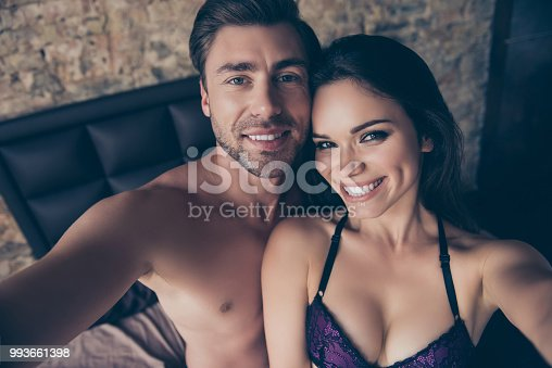 490225014istockphoto Cropped close up portrait of cheerful satisfied excited lovely sensible sensitive cute tender gentle hot bare topless shirtless with toothy smile couple in love taking making selfie in hotel room 993661398