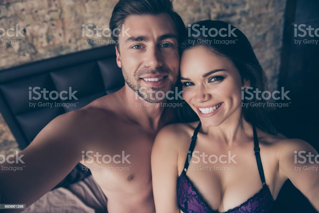 Cropped close up portrait of cheerful satisfied excited lovely sensible sensitive cute tender gentle hot bare topless shirtless with toothy smile couple in love taking making selfie in hotel room stock photo