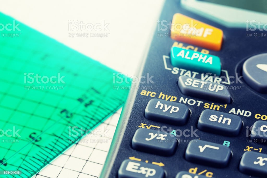 Cropped close-up calculator and set square on graph paper stock photo