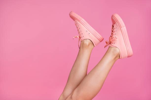 적극적인 스포츠 도보가 단계 유행 발 착용 핑크 파스텔 배경 위에 분리 하는 좋은 매력적인 여성 맞는 얇은 슬림 면도 다리의 클로즈업 이미지 보기 사진 자른 - 신발 뉴스 사진 이미지