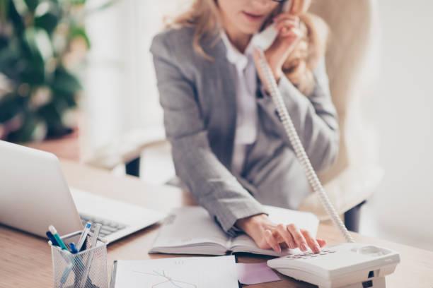 nahaufnahme foto von clever smart professionelle höflich sekretärin in grau, die formellen anzug, ihr chef anruft beschnitten, sitzt sie am tisch im büro - bürorezeption stock-fotos und bilder