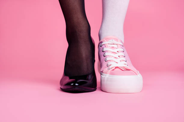 cropped close-up view image concept photo of two different fit thin slim legs cozy comfort luxury luxurious elegant chic sporty comparison footgear isolated on pink pastel background - contrasts stock pictures, royalty-free photos & images