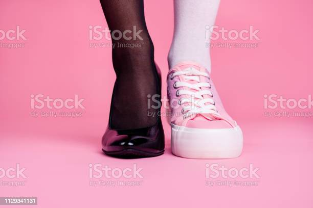 Photo of Cropped close-up view image concept photo of two different fit thin slim legs cozy comfort luxury luxurious elegant chic sporty comparison footgear isolated on pink pastel background