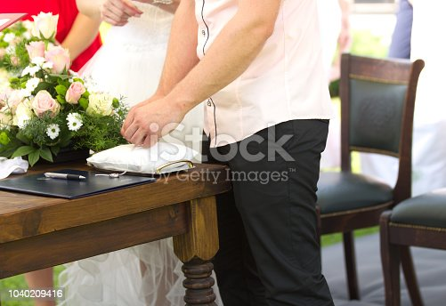 Cropped Groom´s Hands Untying a Wedding Ring