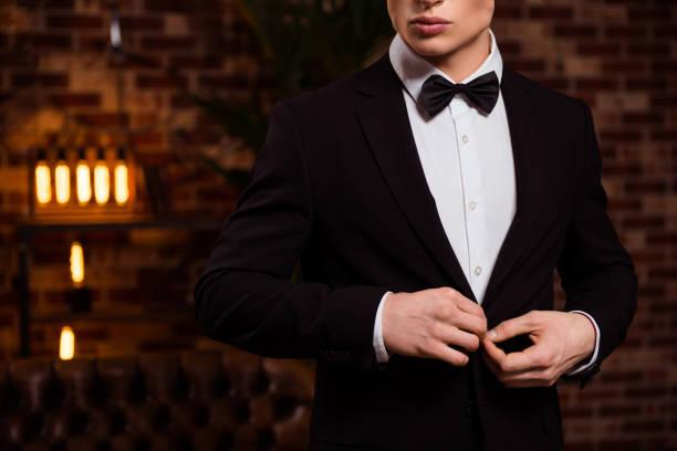 halbe gesicht portrait von manly, harte, virile perfekte mann im schwarzen anzug mit fliege, vorbereitung für datum, korrektur-taste auf jacke über mauer in seinem haus abgeschnitten - bräutigam anzug vintage stock-fotos und bilder