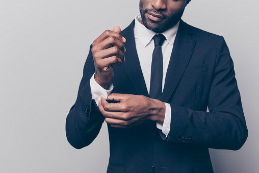 istock Cropped half face portrait of trendy, attractive, stunning man in black tuxedo with tie fasten button on sleeve cuffs of his white shirt, isolated on grey background 931297932