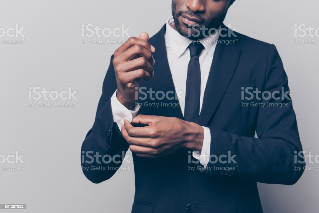 Cropped half face portrait of trendy, attractive, stunning man in black tuxedo with tie fasten button on sleeve cuffs of his white shirt, isolated on grey background stock photo