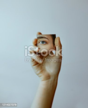 Cropped hand holding mirror with reflection of eye