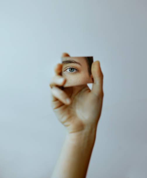 miroir de fixation de main cropped avec le reflet de l'oeil - miroir photos et images de collection