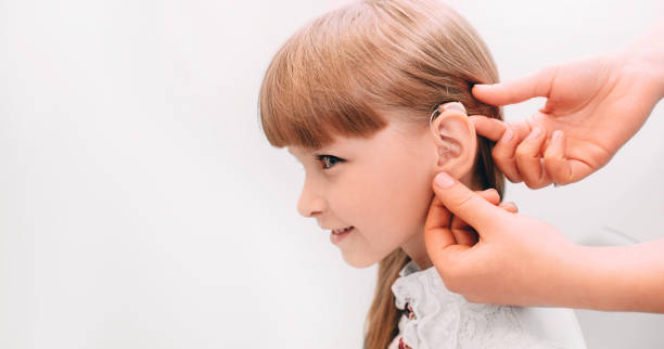 cropped hand of doctor places a hearing aid in the child's ear - hearing loss stock pictures, royalty-free photos & images